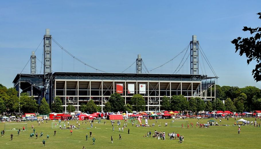 "RheinEnergie-Stadion Südseite. Im Vordergrund Fußballspieler auf der Jahnwiese im Rahmen des ""Come-Together-Cup"" 2011, photo by Raimond Spekking, on Wikimedia, CC BY-SA 4.0"